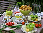 Gedeckter Tisch mit Kartoffeln, Kräuterquark, Tomaten, Salat