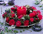 Wreath of red roses and herbs around red candle