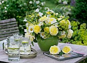 Vase of yellow roses, marguerites and campanulas