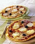 Pizzas topped with goat's cheese and black olives