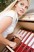 Young woman hiding chocolate between files