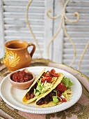 Tacos filled with chili con carne, salad and cheese