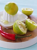 Squeezed limes, citrus squeezer and red chilli