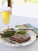 Grilled beef steak, green asparagus and beer