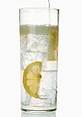 A glass of gin and tonic with slices of lemon