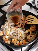Adding fish sauce to a pan of shrimps and glass noodles