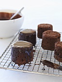 Covering small chocolate cakes with chocolate icing