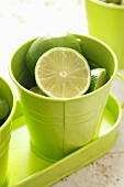 Whole and halved limes in a green beaker