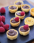 Several pastry shells filled with chocolate mousse & raspberries