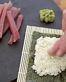 Making tekka maki (Tuna maki sushi)