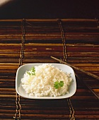Rice in white bowl on brown background