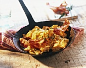 Scrambled egg with bacon & chives in cast-iron frying pan