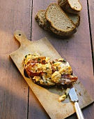 Scrambled egg with bacon and chives on farmhouse bread