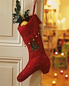 Red felt boot full of gifts on a door