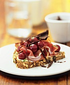Raw ham, cherries and chocolate curls on wholegrain bread