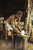 Man shelling a king coconut