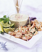 Prawns on cocktail sticks with lime wedges and dip