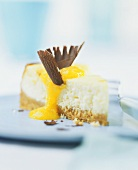 A piece of cheesecake with mango sauce