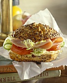 Sliced turkey, tomato, cucumber & lettuce in bread roll with seeds