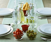 Small dishes of tomatoes and olives on laid table