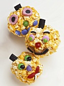 Amusing faces made with caramel popcorn and sweets