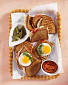 Toasted brown bread with fried eggs, ham and cheese