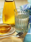 Glass of water, dish of honey and bottle of cider vinegar