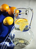 Mineral water with orange and lemon wedges in glass jug