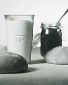 Still life with milk, jam and bread rolls (b-w shot)