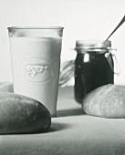 Still life with milk, jam and bread rolls (b-w shot)