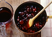 Red berry compote in pan with spoon