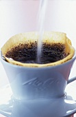 Making filter coffee (pouring water over coffee in filter)
