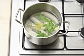 Boiling white sausages (Weisswurst) with lemon peel and parsley