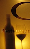 Shadows of a wine bottle and a glass with the word 'restaurant'