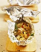 Fish fillets and mushrooms in aluminium foil