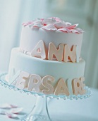 A white, two-tier birthday cake with writing