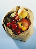 Cherries, apples and strawberries in a paper bag