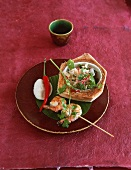 Prawn kebabs with a side salad in a coconut shell