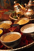 Various spices in dishes (curry, cumin, ginger, coconut)