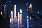 Toasting with champagne glasses by candlelight