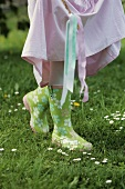 A girl wearing brightly coloured wellie boots in a field
