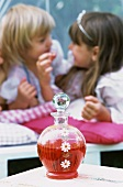 A bottle of strawberry juice with two girls in the background