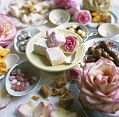 Different sorts desserts and candies decorated with rose petals