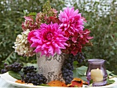 An autumnal bouquet of dahlias with grapes and lanterns on a garden table