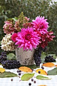 An autumnal bouquet of flowers and red grapes on a garden table