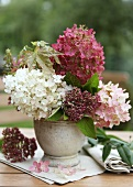 An autumnal bouquet of hortensias on a garden table