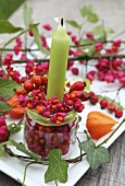 A candle in a glass with spindle and rosehips decorating the table