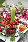 Kerze im Glas mit Pfaffenhütchen und Hagebutten als Tischdeko