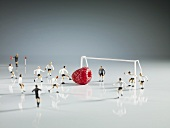 Miniature footballers playing with a raspberry