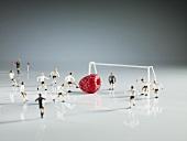 Fussballer-Figuren spielen mit einer Himbeere